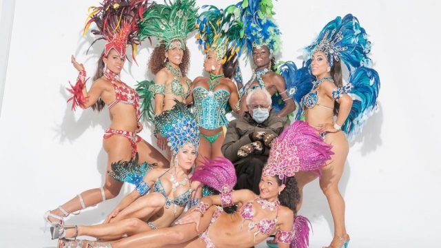 SambaViva dancers in full Carnaval costume with Bernie Sanders sitting in the middle wearing a coat and mittens
